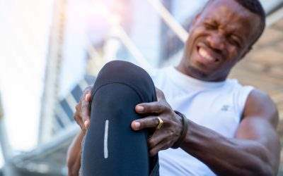 man gripping his knee in pain